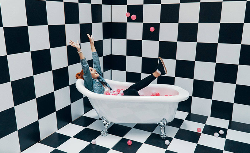 Woman in bath tub ball pit at Bristol Selfie Factory