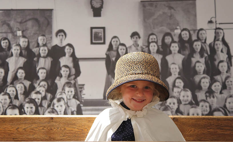 Girl in orphan uniform in front of school room photo at George Müller Museum