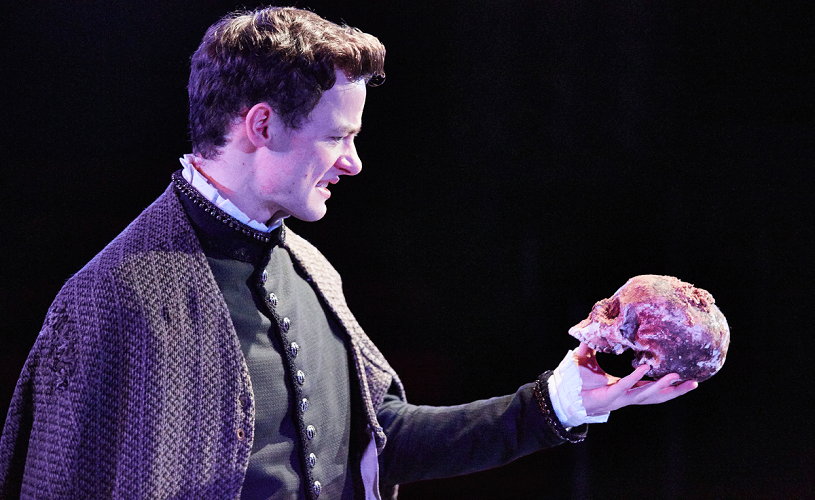 Man holding skull in performance of Hamlet