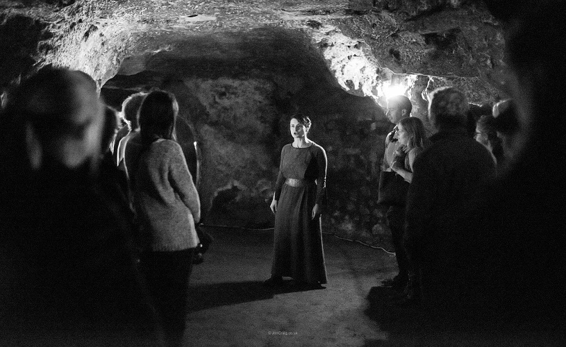 Woman performing in Macbeth, in Redcliffe Caves, Bristol.