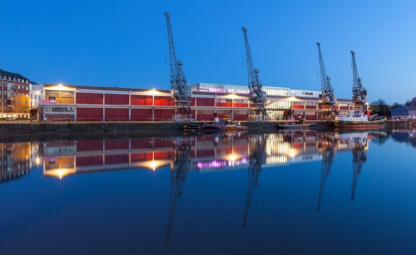 M Shed and three cranes reflected on the water at Bristol Harbourside