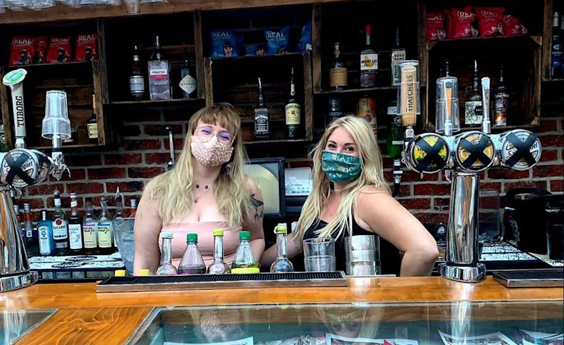 Staff in face masks behind bar at Mr Wolf's