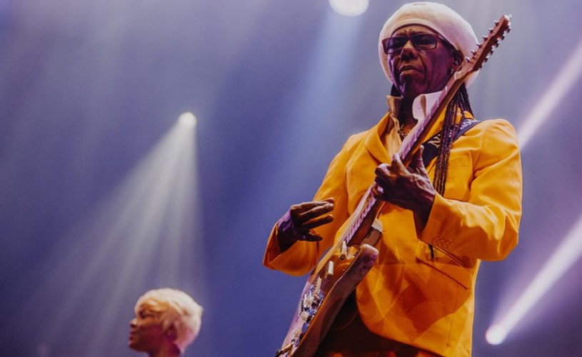 Nile Rodgers on stage playing guitar