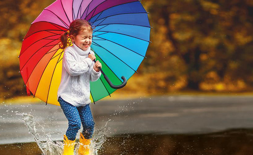 Girl with umbrella jumping in puddles - Slimbridge Puddle Jumping Championships
