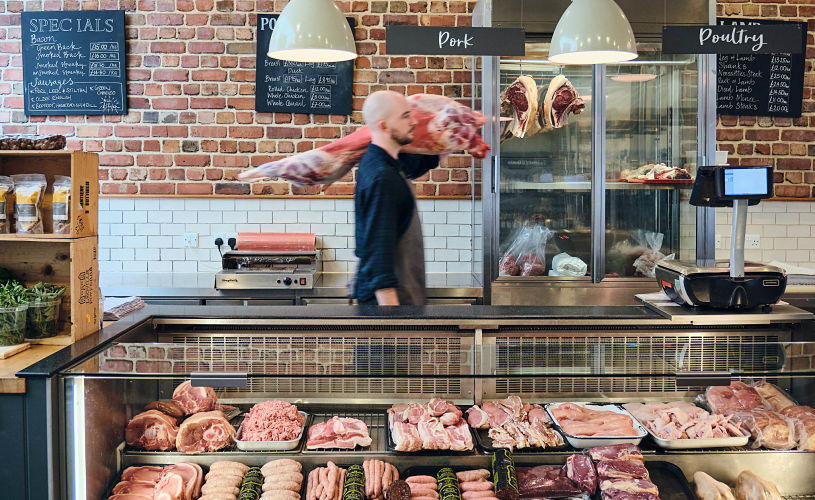 Man carrying cut of meat at Ruby & White butcher in Bristol