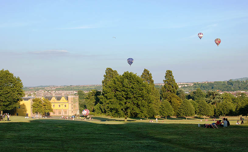 Lawns outside Ashton Court and hot air balloons flying over