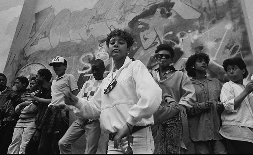 Group of people in front of wall of graffiti at St Paul's Carnival, 1986