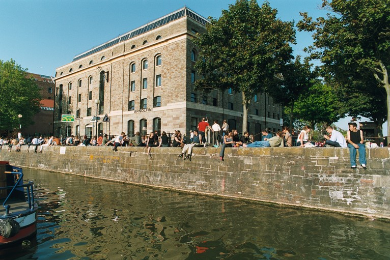 People sitting on the Harbourside wall outside Arnolfini, Bristol