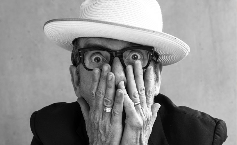 Elvis Costello with a white hat and hands on his face