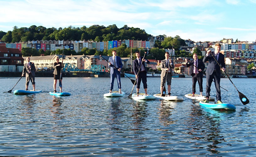 Employees in suits on stand up paddle boards with Bristol's colourful houses in the background