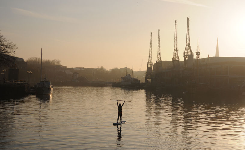 Woman stand up paddle boarding on a misty morning on Bristol Harbourside