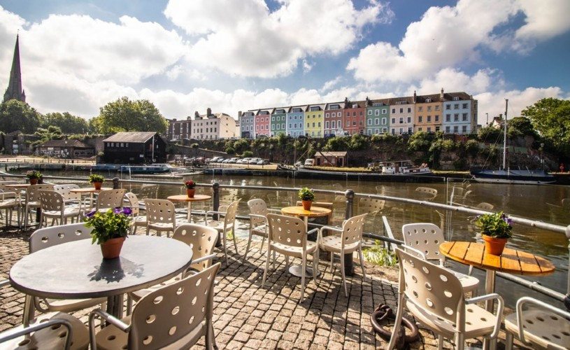 Tables and chairs on Riverstation's terrace overlooking the Harbour and a row of colourful houses