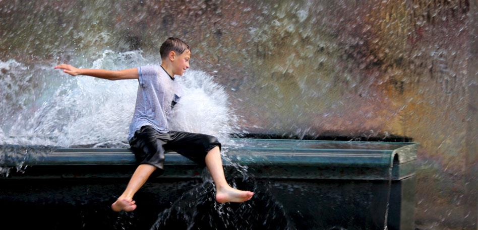 Boy playing in water fountains in Millennium Square Bristol - Image Marilyn Reynolds