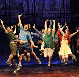 Group shot of cast in Blood Brothers jumping up on stage