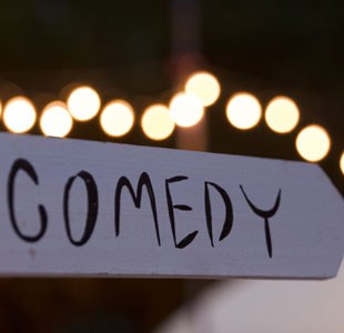 The word comedy on sign post